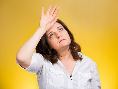 woe: Closeup portrait annoyed tired middle aged woman placing back hand on forehead, tragedy of it all, woe is me, exaggerating isolated yellow background. Negative emotion, facial expression, perception