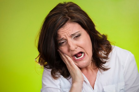 Closeup portrait middle aged woman with sensitive tooth ache crown problem crying from pain touching outside mouth isolated green background. Negative emotion facial expression feeling health issue photo