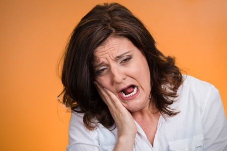 health issue: Closeup portrait middle aged woman with sensitive tooth ache crown problem crying from pain touching outside mouth isolated orange background. Negative emotion facial expression feeling health issue