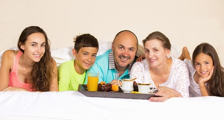 Group portrait looking happy smiling joyful family, mother, father, daughters, son having breakfast in bed, surprise on mom day. Positive human emotions, face expressions, feelings, life perception. photo