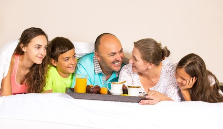 Group portrait looking happy smiling joyful family, mother, father, daughters, son having breakfast in bed, surprise on mom day. Positive human emotions, face expressions, feelings, life perception.