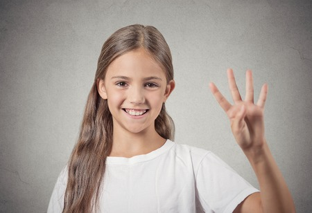 Closeup portrait excited happy teenager girl showing 4 fingers, giving number four sign isolated grey wall background. Positive emotion face expressions, feelings, attitude, perception body language photo