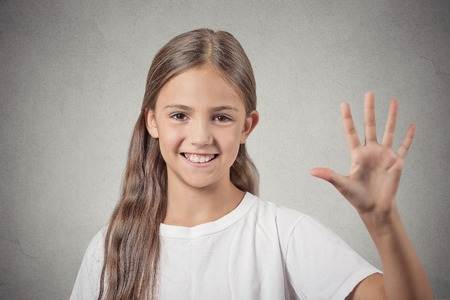appraising: Closeup portrait headshot happy smiling teenager girl making five times sign gesture with hand fingers isolated grey wall background. Positive human emotion facial expression symbol body language sign