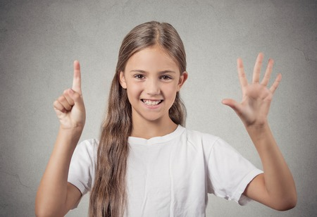 graduation countdown: Closeup portrait excited happy teenager girl showing 6 fingers, giving number six sign, isolated grey background. Positive human emotion face expression, attitude, reaction, perception body language