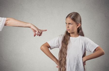 autoridad: Retrato del primer padre señalando a los niños en la camiseta blanca regaño ir a la sala de conexión a tierra por portarse mal mientras niño está mirando las manos en las caderas, desobedientes aislado fondo de la pared gris. La emoción negativa