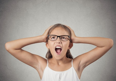 errands: Closeup portrait stressed, overwhelmed teenager girl with glasses hands on head screaming going crazy isolated grey wall background. Negative human emotions, facial expressions, reaction, feelings Stock Photo
