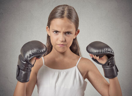 Aggressive child teenager girl wearing boxing gloves ready to fight isolated grey wall background. Negative human emotions, face expressions, feelings photo