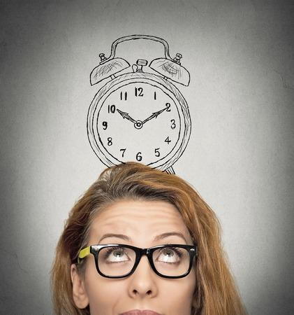 tempo: closeup headshot jovem mulher de negócios com o desenho despertador esboço acima de sua cabeça, isolado fundo cinzento parede. Expressões faciais humanas, emoções. Tempo, pontualidade, conceito agenda lotada