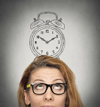 time pressure: closeup headshot young business woman with alarm clock drawing sketch above her head, isolated grey wall background. Human face expressions, emotions. Time, punctuality, busy schedule concept