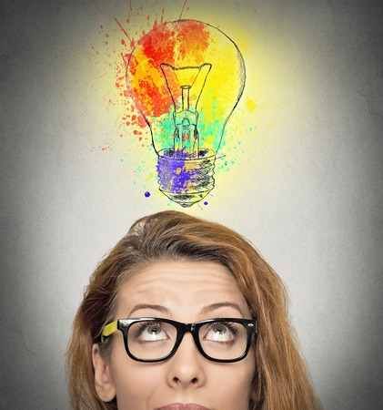 woman having brilliant idea colorful lightbulb above head, isolated grey wall background. Human face expressions, emotions, feelings. Creativity, imagination, dynamism, intelligence concept
