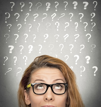 Headshot beautiful woman with puzzled face expression and question marks above her head looking up, isolated grey wall background. Human emotions, feelings, body language, problem solution concept