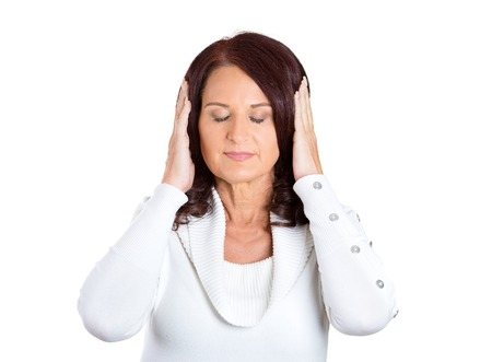 Closeup portrait attractive, peaceful, relaxed looking, middle aged woman covering ears, closing her eyes, isolated white background. Hear no evil concept. Human emotions, facial expression, attitude Stock Photo