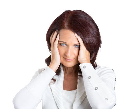 Closeup portrait unhappy stressed middle aged business woman hands on heads bothered by mistake, having bad headache isolated on white background. Negative human emotion facial expression feelings photo