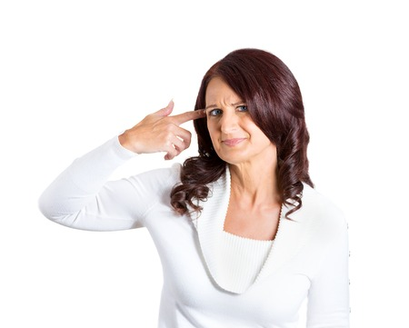 Closeup portrait rude, difficult angry mature woman, gesturing with finger against temple, are you crazy? Isolated white background. Negative human emotions, facial expression, feeling, attitude Stock Photo