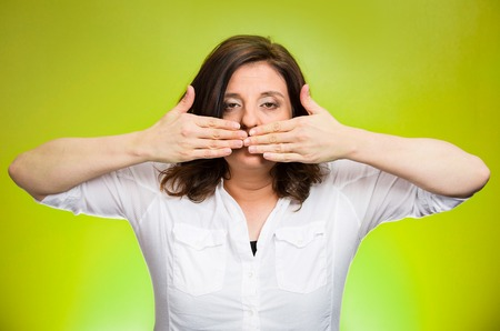 Closeup portrait middle aged woman covering closed mouth. Speak no evil concept, isolated green background. Negative human emotion facial expressions, sign, symbol. Media news coverup, censorship