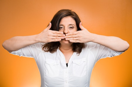 censor: Closeup portrait middle aged woman covering closed mouth. Speak no evil concept, isolated orange background. Negative human emotion facial expressions, sign, symbol. Media news coverup, censorship Stock Photo