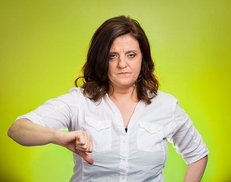 pessimist: Closeup portrait unhappy, angry, mad, pissed off woman, giving thumb down hand gesture with hand looking with negative facial expression, disapproval isolated green background. Human emotion attitude