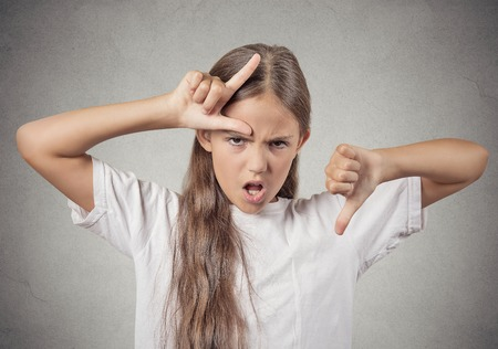bad manners: Closeup portrait angry mad upset pissed off teenager girl showing loser sign giving thumbs down isolated grey wall background. Negative emotion facial expression sign symbols feeling body language