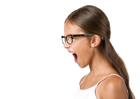 side view portrait angry child screaming wide open mouth isolated white background. Negative human face expression emotion reaction, perception, body language. Conflict, confrontation concept photo