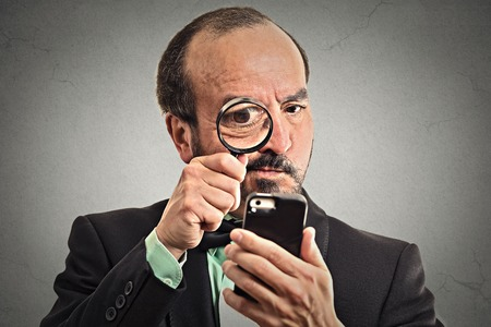 company secrets: Curious. Mature business man looking through a magnifying glass on smart phone isolated grey wall background. Human face expression. Investigator looking with magnifying glass. Security safety concept