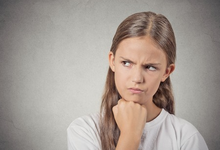disobey: Closeup portrait angry grumpy teenager girl displeased jealous looking to side isolated grey wall background. Negative human emotions facial expression feeling attitude reaction body language Stock Photo