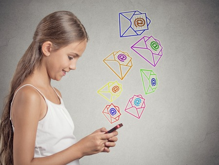 smiling teenager girl standing holding smart phone texting, sending message, email icons coming out of mobile phone isolated grey wall background. telecommunications, internet, 4g data plan concept photo