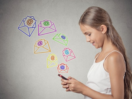 web side: smiling teenager girl standing holding smart phone texting, sending message, email icons coming out of mobile phone isolated grey wall background. telecommunications, internet, 4g data plan concept