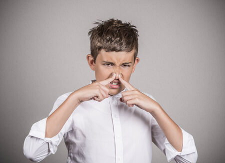 Closeup portrait young man with disgust on face, pinches his nose, something stinks, bad smell, situation isolated grey wall background. Negative emotions, facial expressions, perception body language Stock Photo