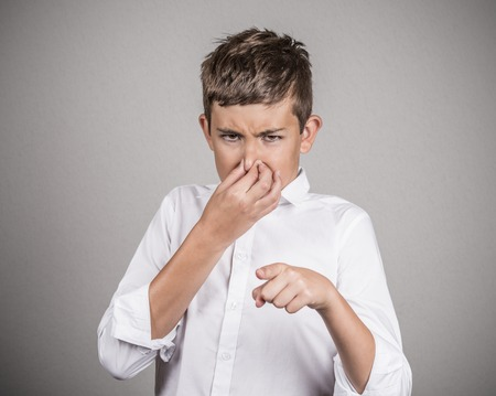 fart: Closeup portrait young man with disgust on face pinches his nose, something stinks bad smell, pointing finger isolated grey background. Negative emotion facial expression perception body language Stock Photo