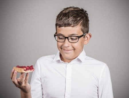 cravings: Carbs cravings. Portrait teenager boy craving cake confused funny looking man trying to withstand resist temptation to eat sweet tart isolated grey background. Facial expression emotion reaction