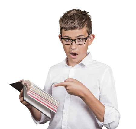 rumor: Closeup portrait young man with glasses, wide opened eyes mouth pointing at book page shocked surprised by  twists, turn of story, isolated white background. Human emotion facial expression reaction Stock Photo