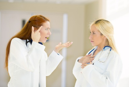 health care professionals physicians nurses fighting screaming at each other in a hospital hallway. negative human emotions, face expressions, feelings, body language, bad attitude, confrontation