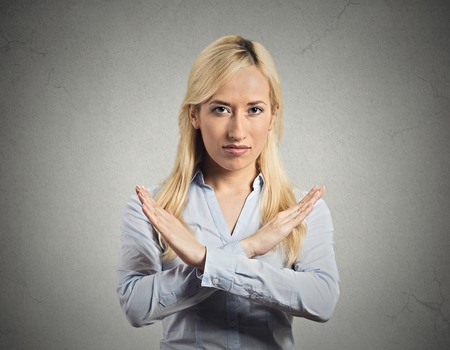 admonish: Closeup portrait angry young woman with X gesture to stop talking, cut it out, dont go there, isolated grey wall background. Negative emotion facial expression feeling sign symbols, body language