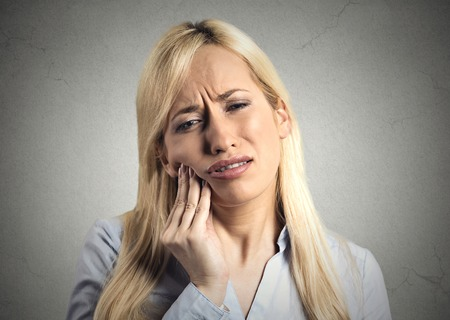 gingivitis: Closeup portrait young woman with sensitive tooth ache crown problem about to cry from pain touching outside mouth with hand, isolated grey wall background. Negative emotion facial expression feeling
