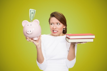 cost of education: Cost of college education. Portrait stressed woman balancing piggy bank in one hand and books in another. Student having trouble paying for academic university degree tuition concept. Face expressions
