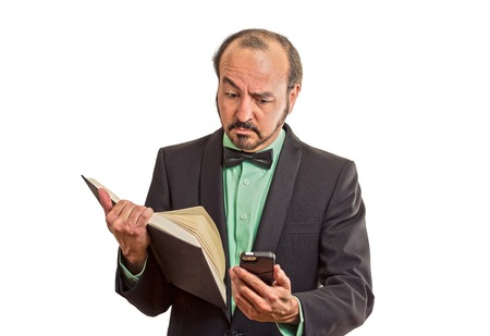 simultaneous: Closeup portrait confused, skeptical business man, executive reading news on smart phone, holding book isolated on white background. Human face expression, emotion, body language, corporate lifestyle Stock Photo