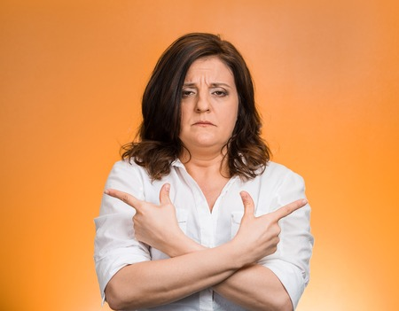 befuddled: Closeup portrait confused middle aged woman pointing in two different directions, not sure which way to go in life isolated orange background. Negative emotion facial expression feeling body language Stock Photo