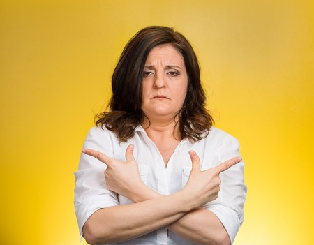 befuddled: Closeup portrait confused middle aged woman pointing in two different directions, not sure which way to go in life isolated yellow background. Negative emotion facial expression feeling body language