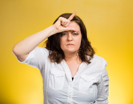 bother: Loser. Closeup portrait funny mature middle aged woman giving loser sign on forehead, looking at you disgust on face isolated yellow background. Negative human emotion facial expression body language