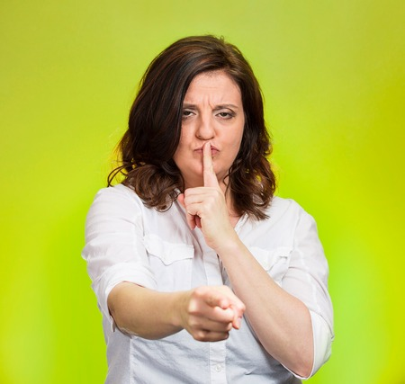 shush: Quiet, patronize. Closeup portrait middle age woman placing finger on lips with shhh sign symbol, asking silence isolated green background. Negative emotion facial expression feelings, body language