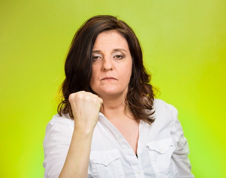 cranky: Closeup portrait angry cranky upset middle aged woman worker business employee putting up fist warning someone stay away isolated green background. Negative emotion facial expression feeling reaction
