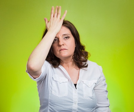 duh: Closeup portrait confused young woman placing hand on head, palm on face gesture in duh moment isolated green background. Negative emotion facial expression feeling body language, life perception Stock Photo