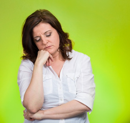 bothered: Depressed, gloomy. Closeup portrait unhappy middle age woman head on hand bothered by mistake situation having bad headache isolated green background. Negative human emotion facial expression feeling