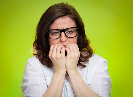 socially: Closeup portrait headshot nervous, stressed middle aged woman with glasses biting fingernails looking anxiously, craving for something isolated green background. Human emotion face expression feeling