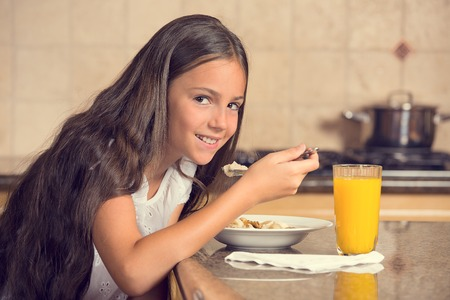 cute teenager girl eating cereal with milk drinking orange juice for breakfast in the kitchen Stock Photo