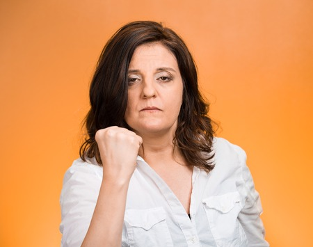 aggravated: Closeup portrait angry cranky upset middle aged woman worker business employee putting up fist warning someone stay away isolated orange background. Negative emotion facial expression feeling reaction