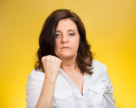aggravated: Closeup portrait angry cranky upset middle aged woman worker business employee putting up fist warning someone stay away isolated yellow background. Negative emotion facial expression feeling reaction