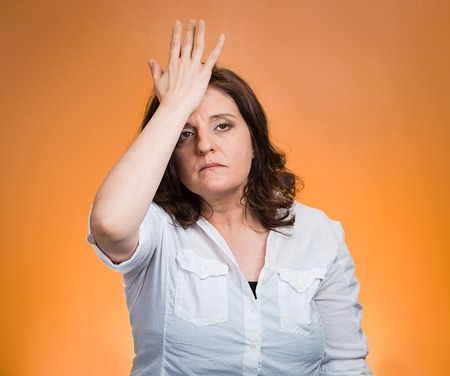 duh: Closeup portrait confused young woman placing hand on head, palm on face gesture in duh moment isolated orange background. Negative emotion facial expression feeling body language, life perception