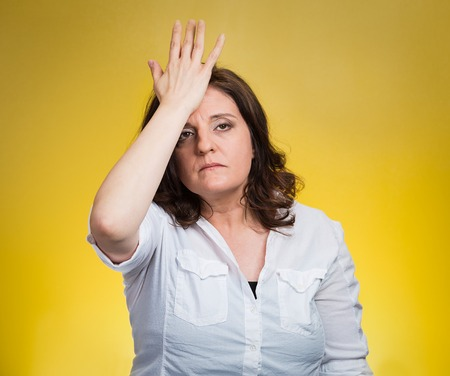 duh: Closeup portrait confused young woman placing hand on head, palm on face gesture in duh moment isolated yellow background. Negative emotion facial expression feeling body language, life perception