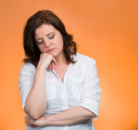 Depressed, gloomy. Closeup portrait unhappy middle age woman head on hand bothered by mistake situation having bad headache isolated orange background. Negative human emotion facial expression feeling photo